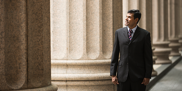 A man in a suit surrounded by stone pillars
