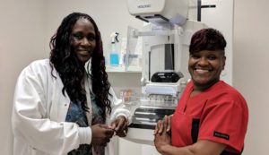 Two female medical professionals posing in front of a piece of medical equipment