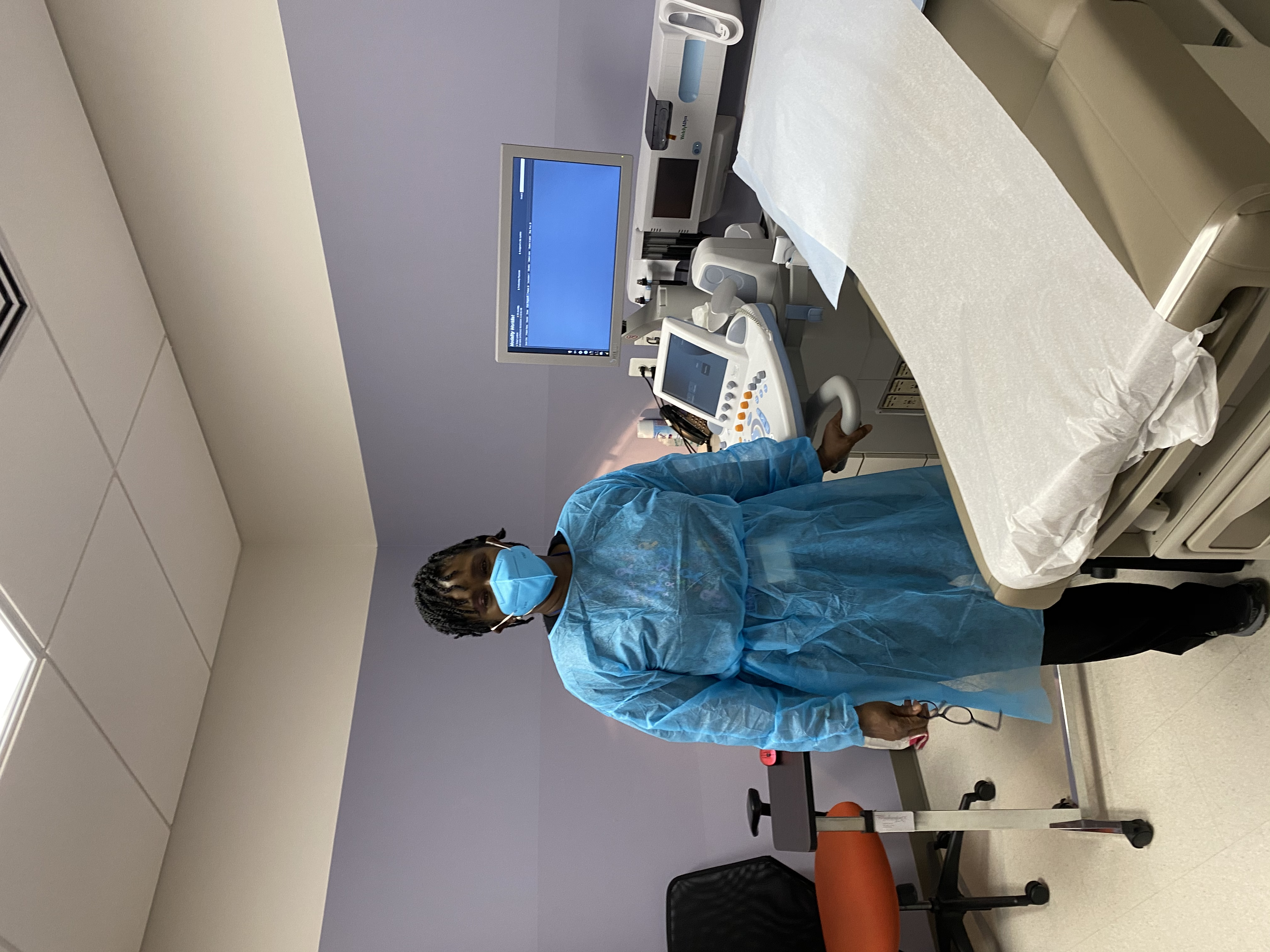 A woman in an exam room wearing a mask and gown