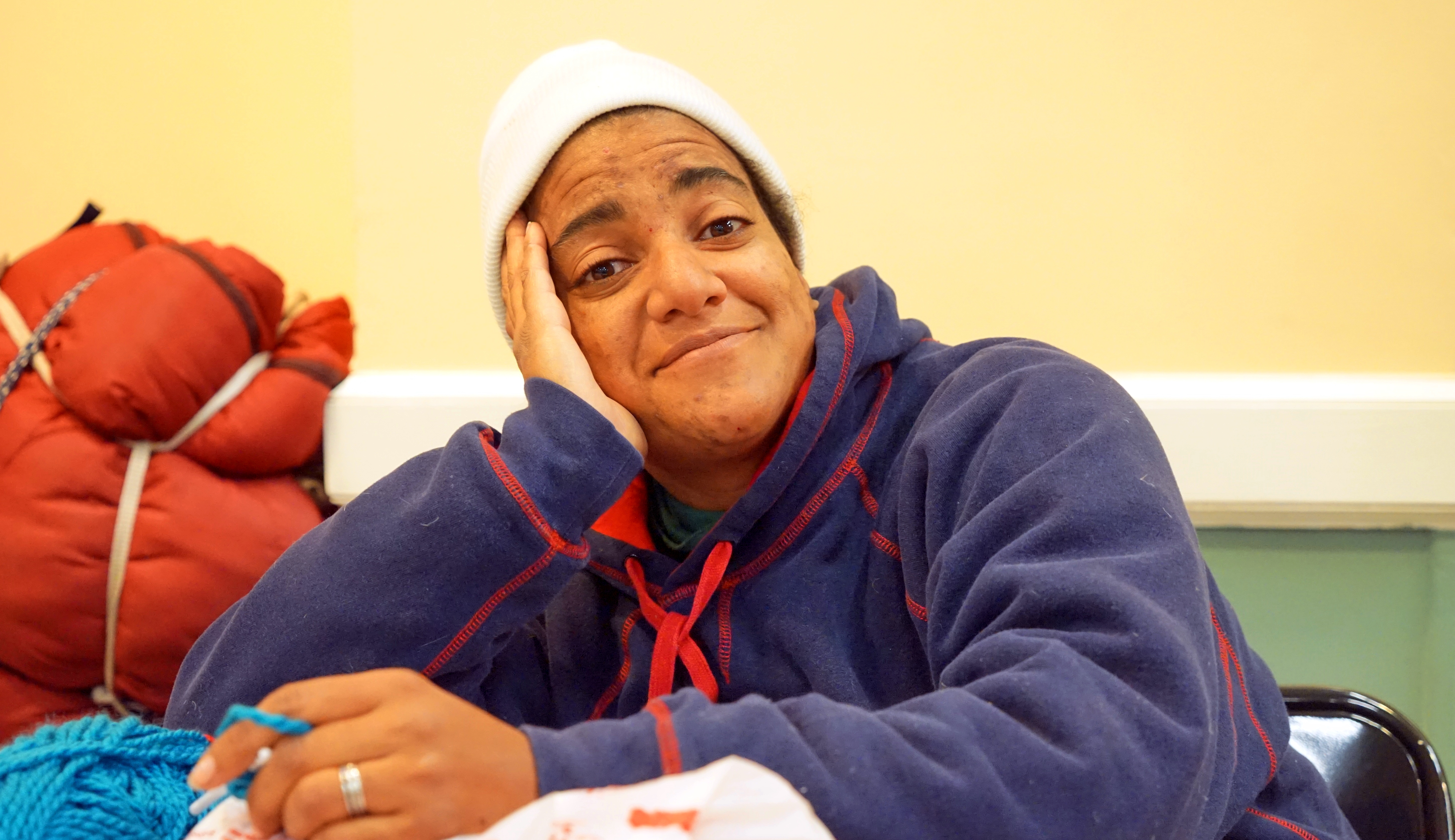 A smiling homeless woman with her elbow propping her head up on a table.