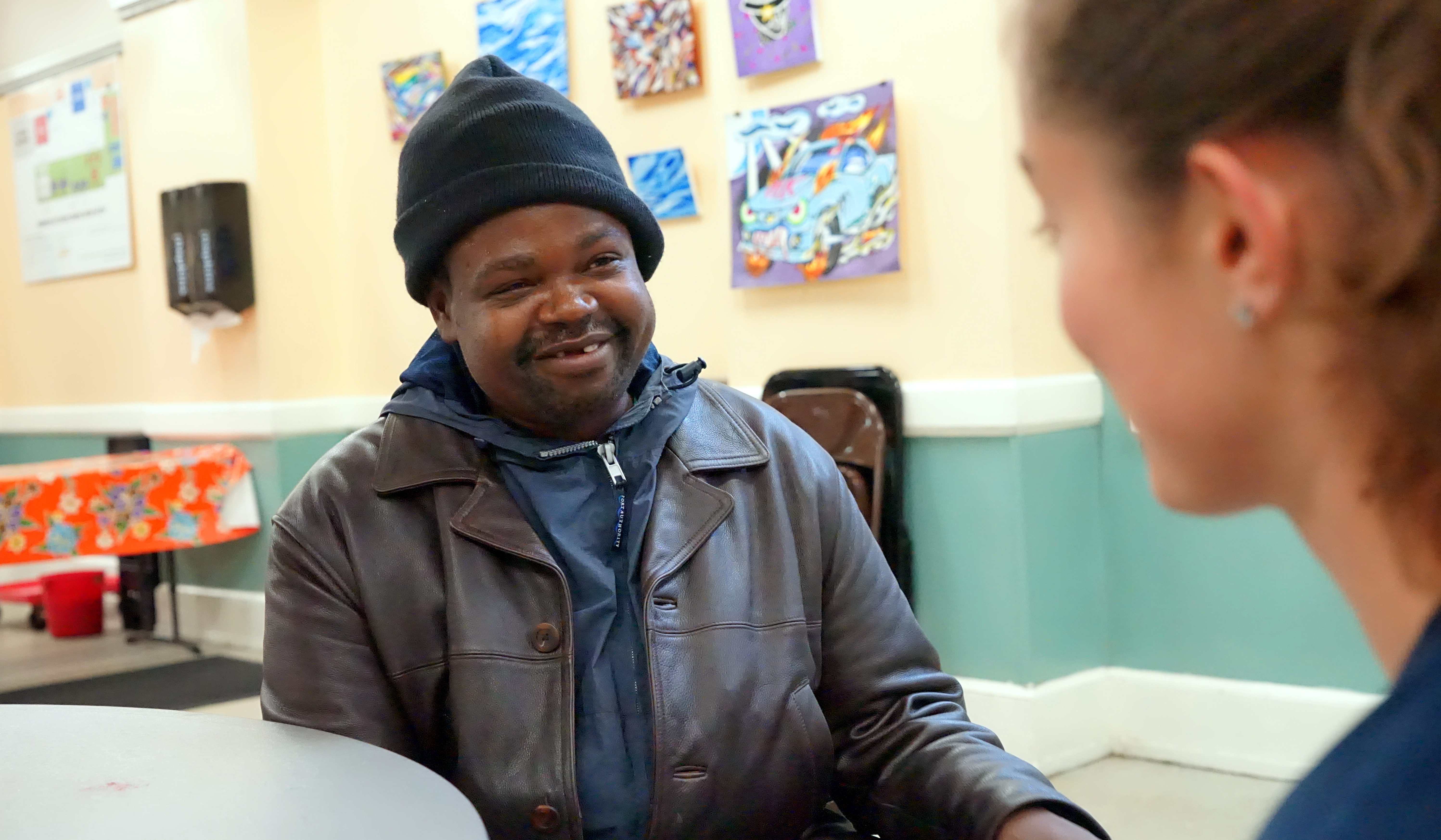 A homeless man smiling with talking with a woman