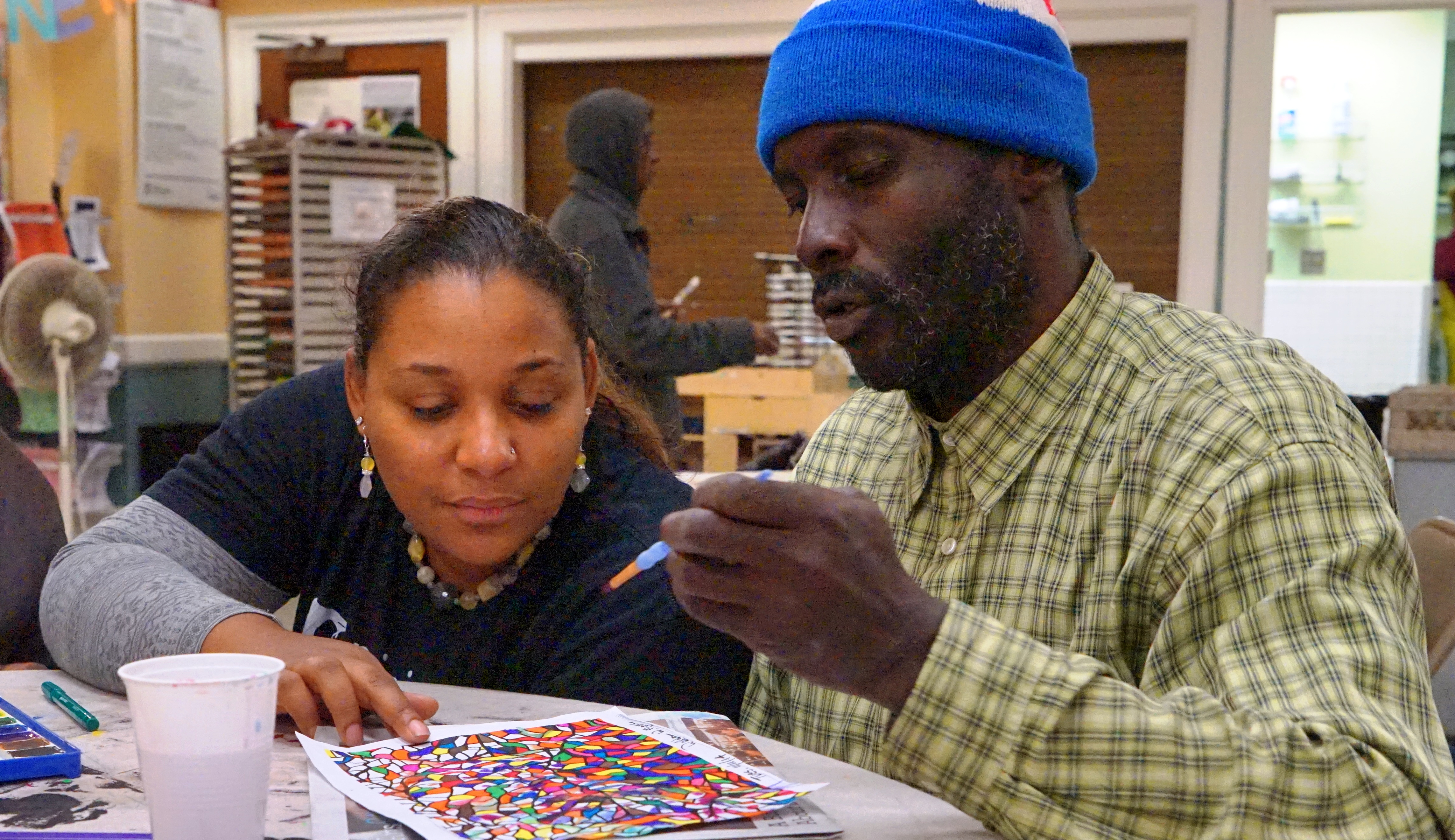 A woman pointing at a piece of artwork on a table that a homeless man is coloring