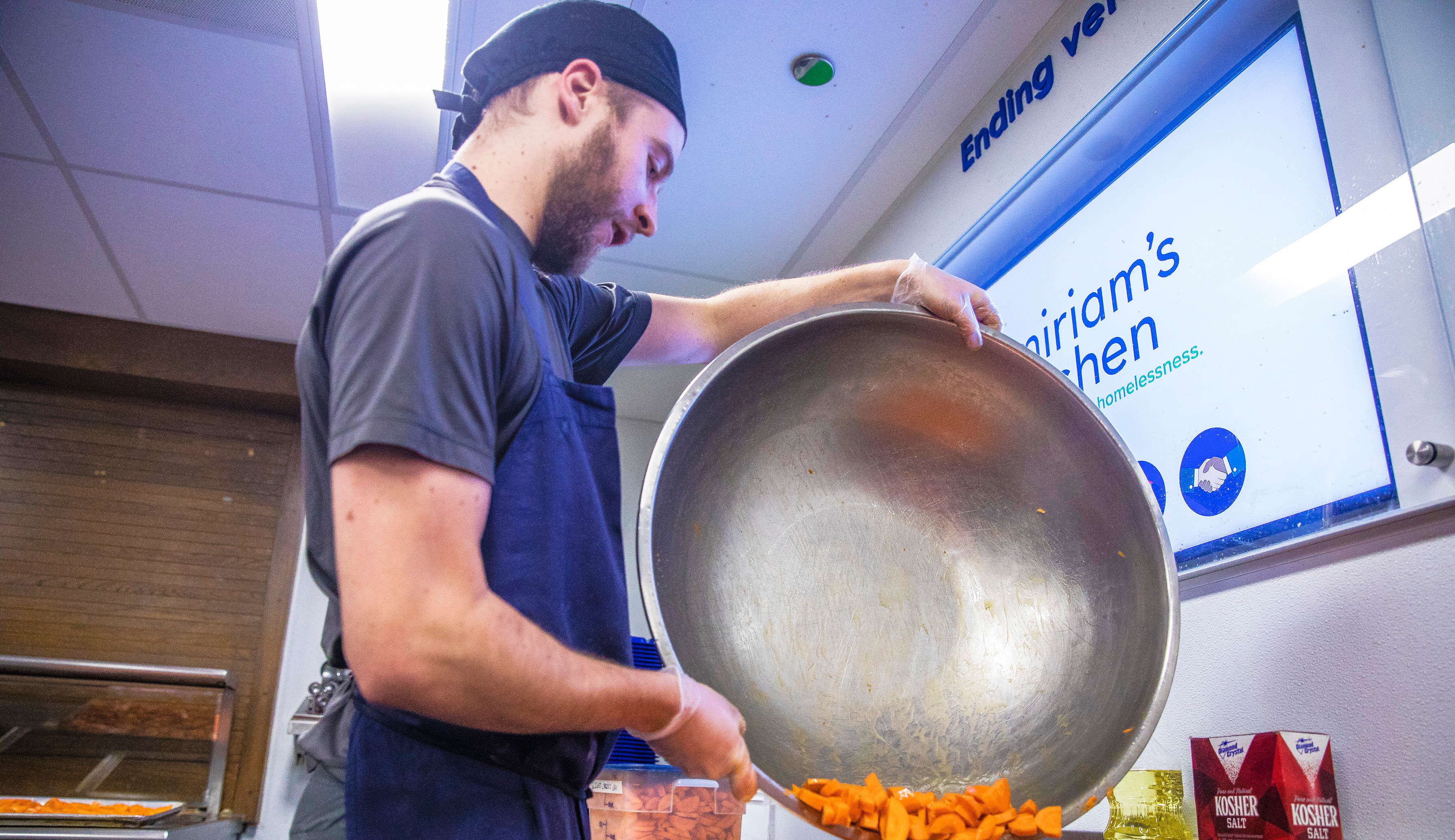 A kitchen worker dumping a large metal bowl of chopped carrots