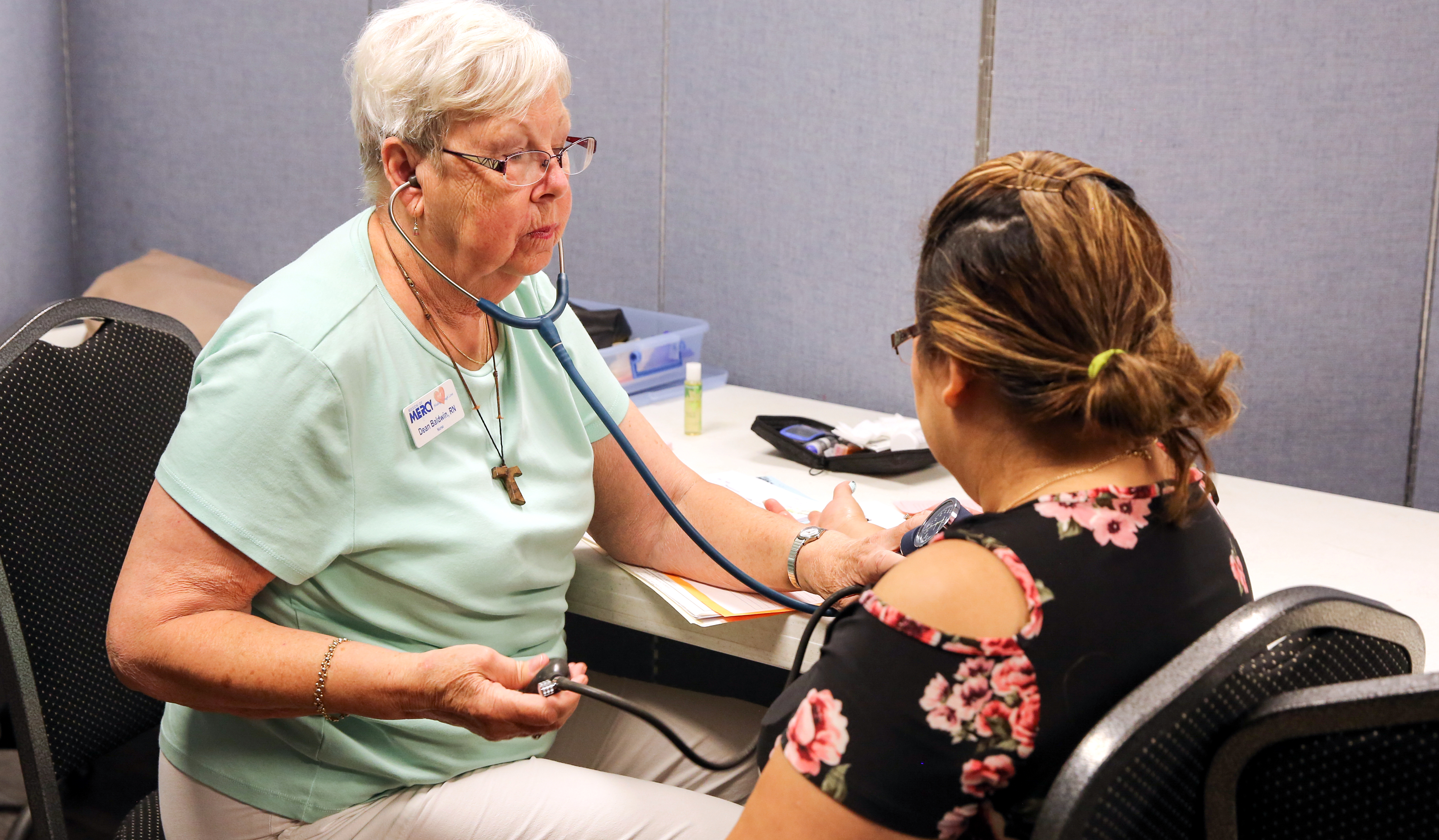 An older woman takes the blood pressure of a client