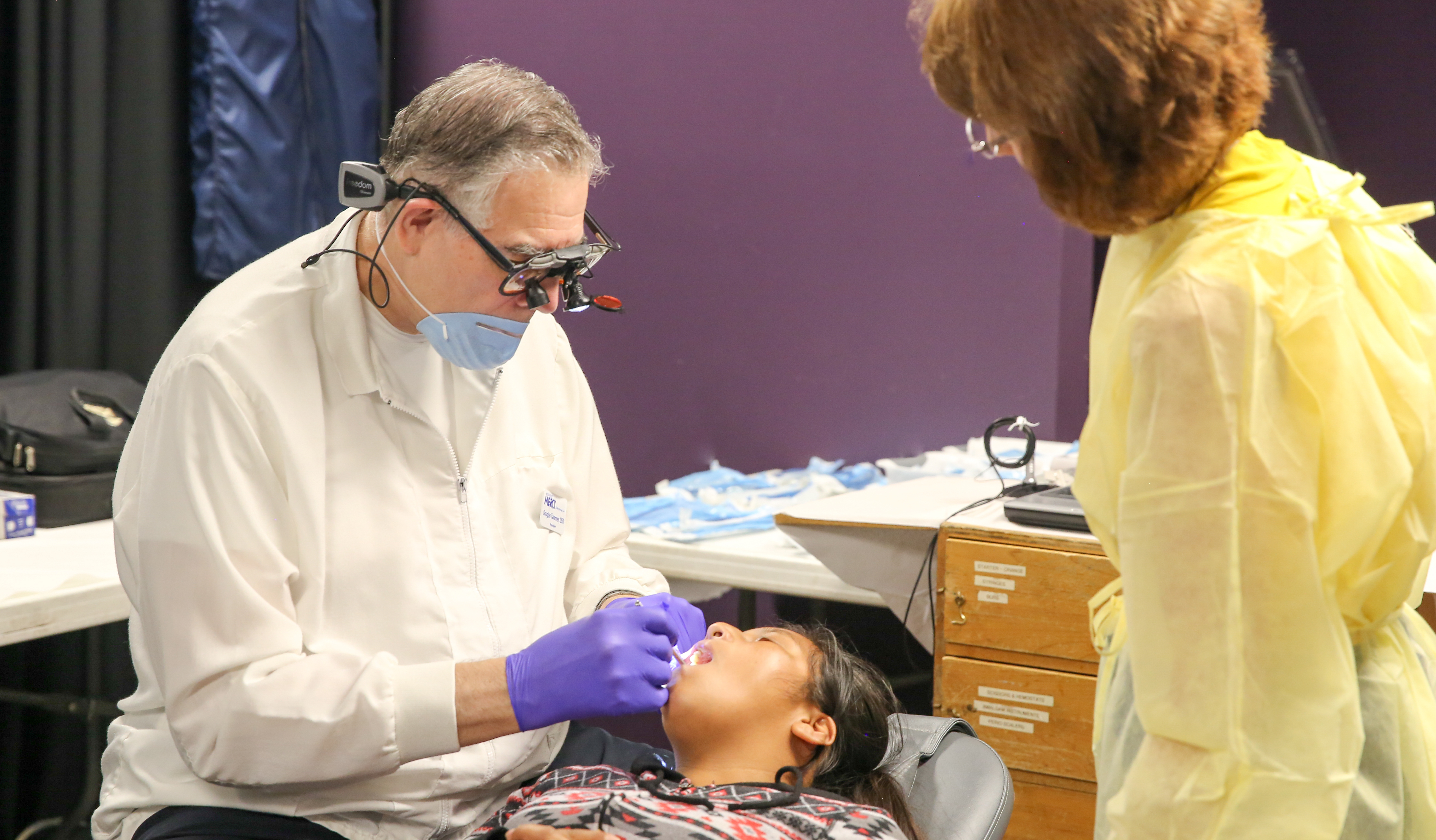 an older dentist examines a patients teeth while a woman looks on