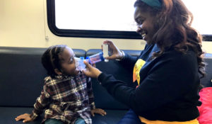 A mother holds a breathing device to her child's mouth inside the Breathmobile