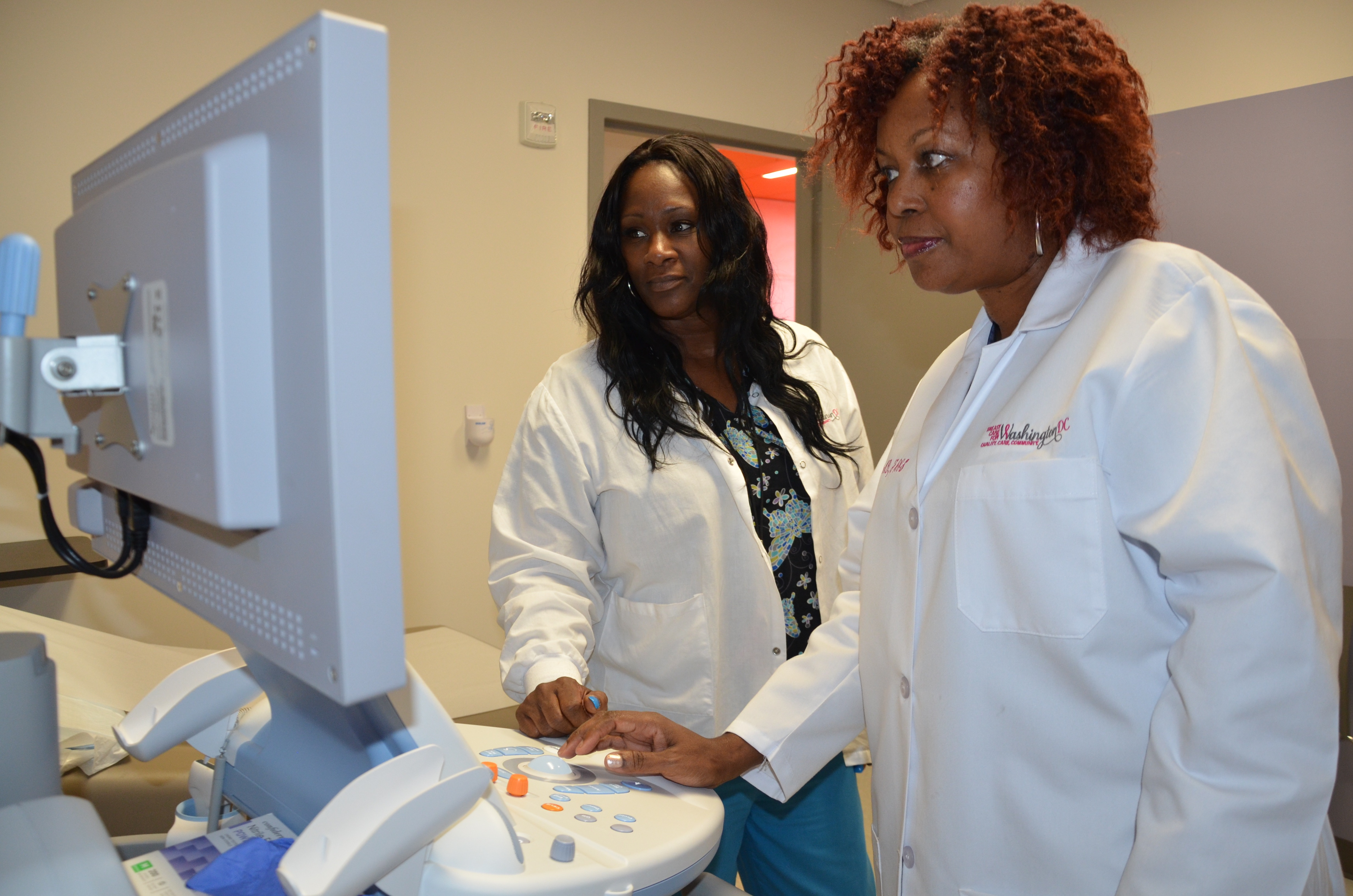Two black female medical providers reading a screen on a medical device