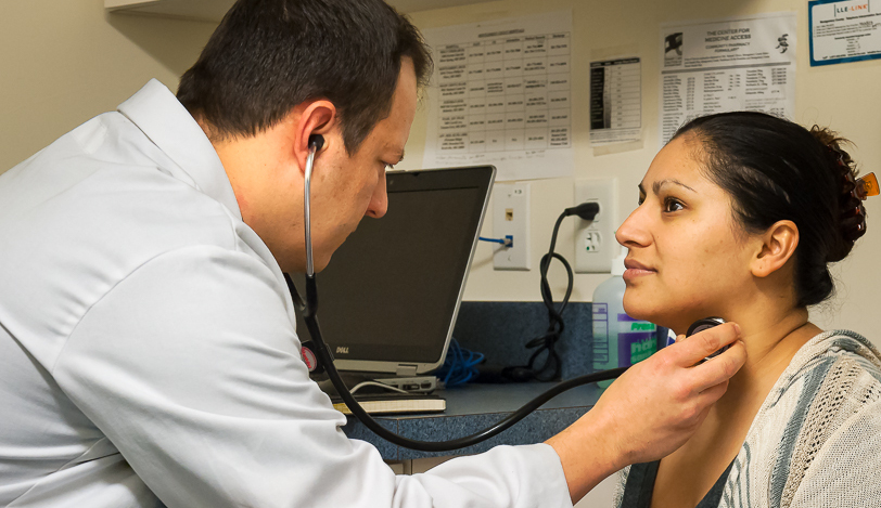 Medial professional using a stethoscope on the neck of a patient