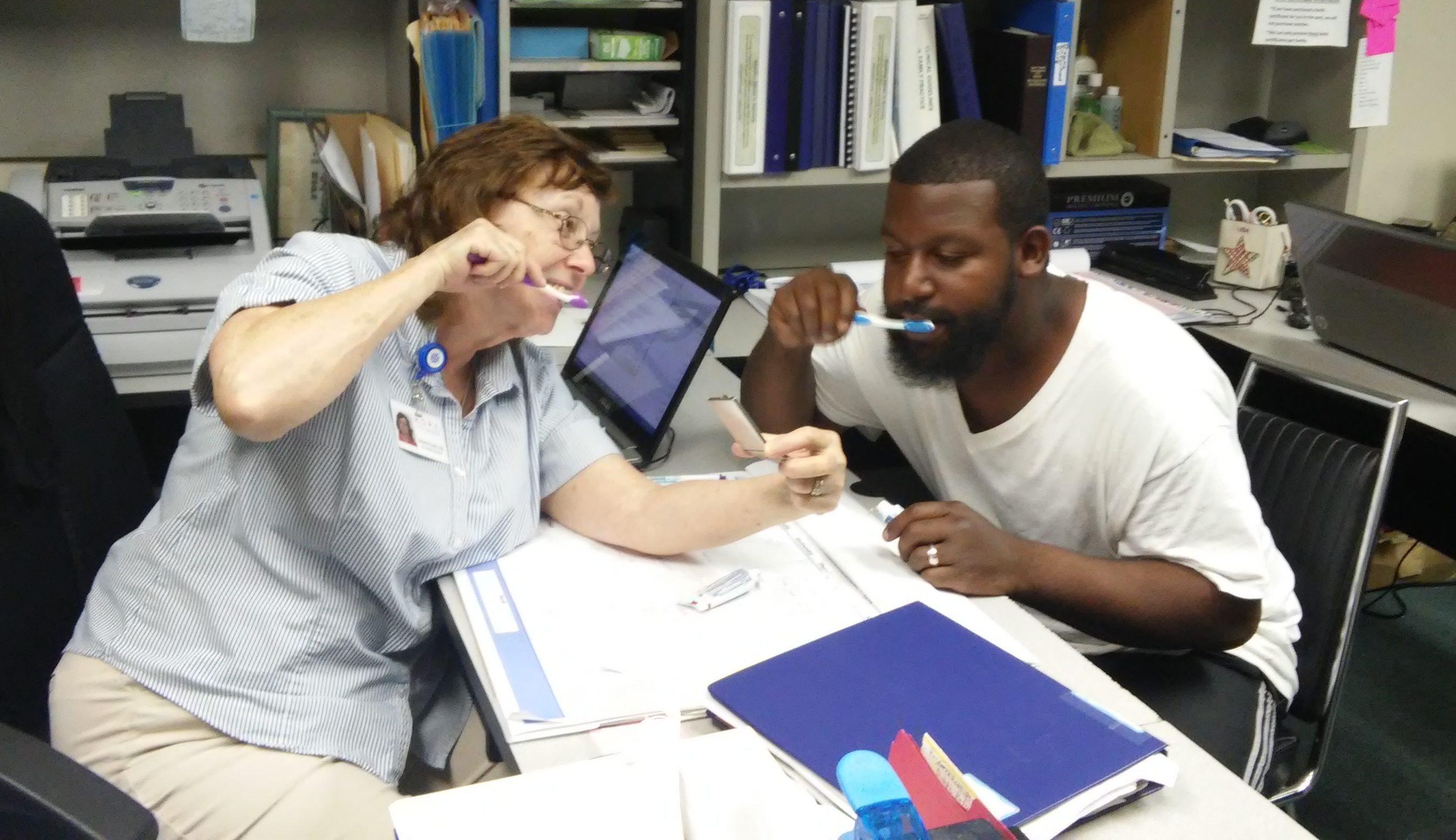A man and woman at a desk practicing brushing their teeth