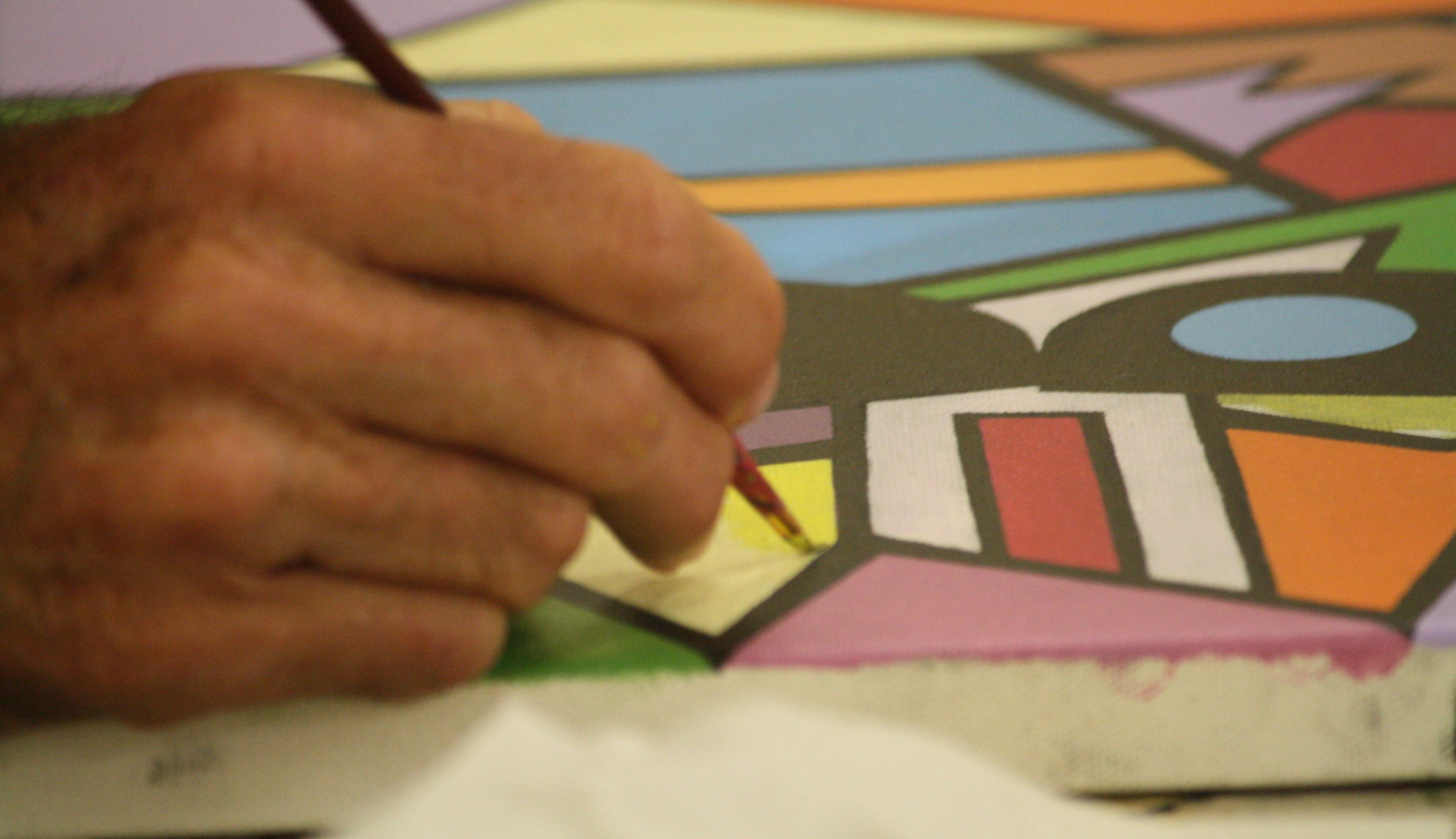 A hand painting art with a brush onto a thick piece of board