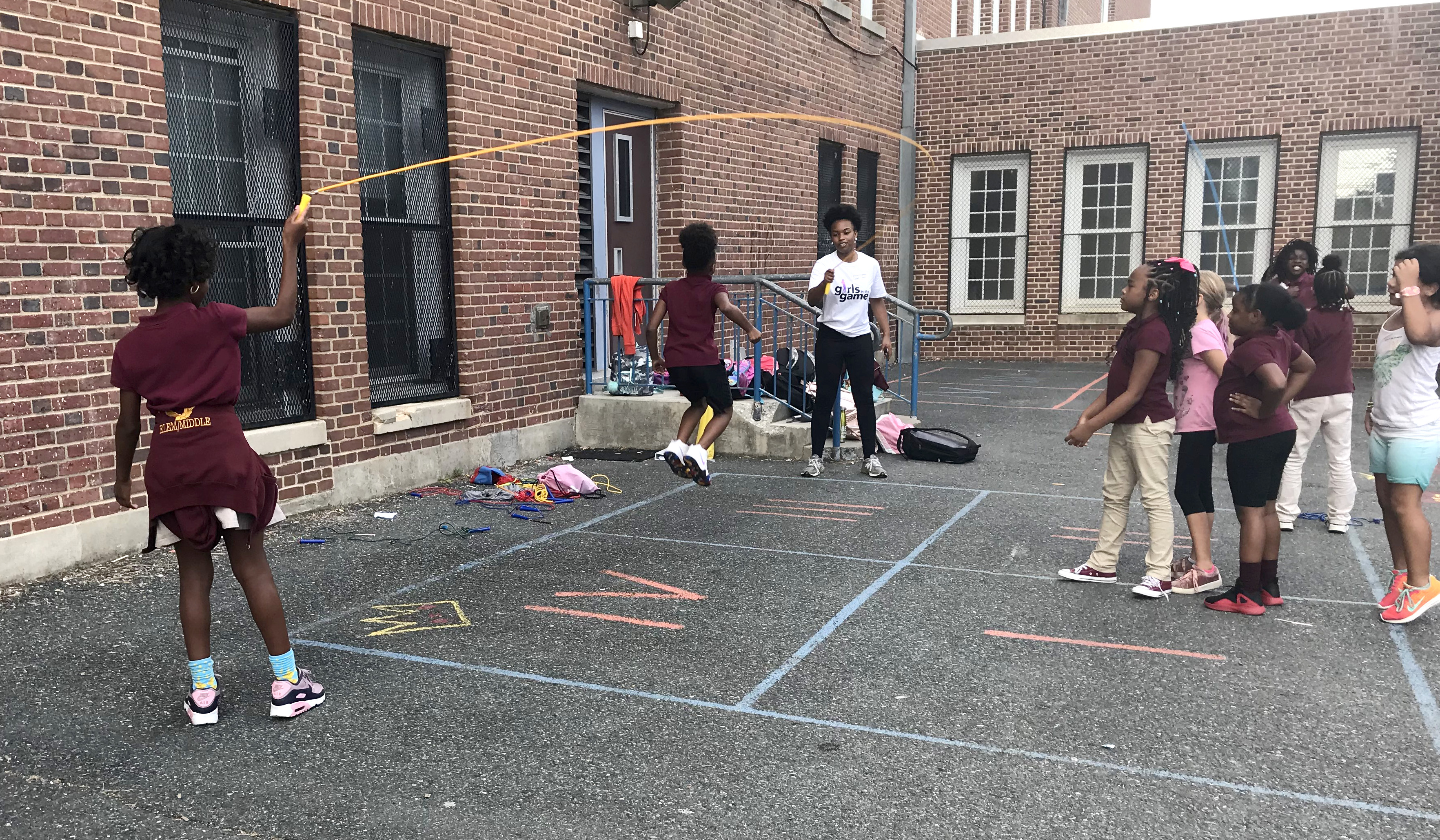 Girls play jump rope on a playground lot