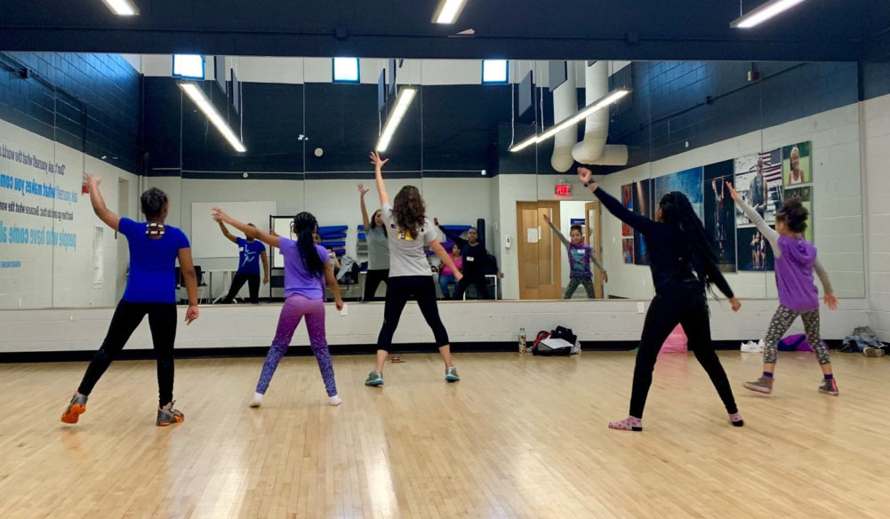 girls practice aerobics in a gym setting