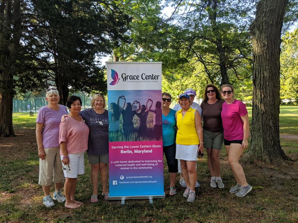 group of women with a pull up banner for Grace Center