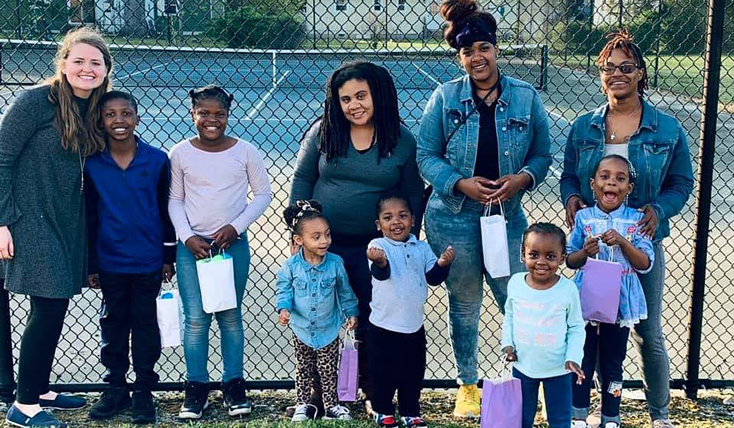 Group of mothers with children against a fence holding egg hunt baskets
