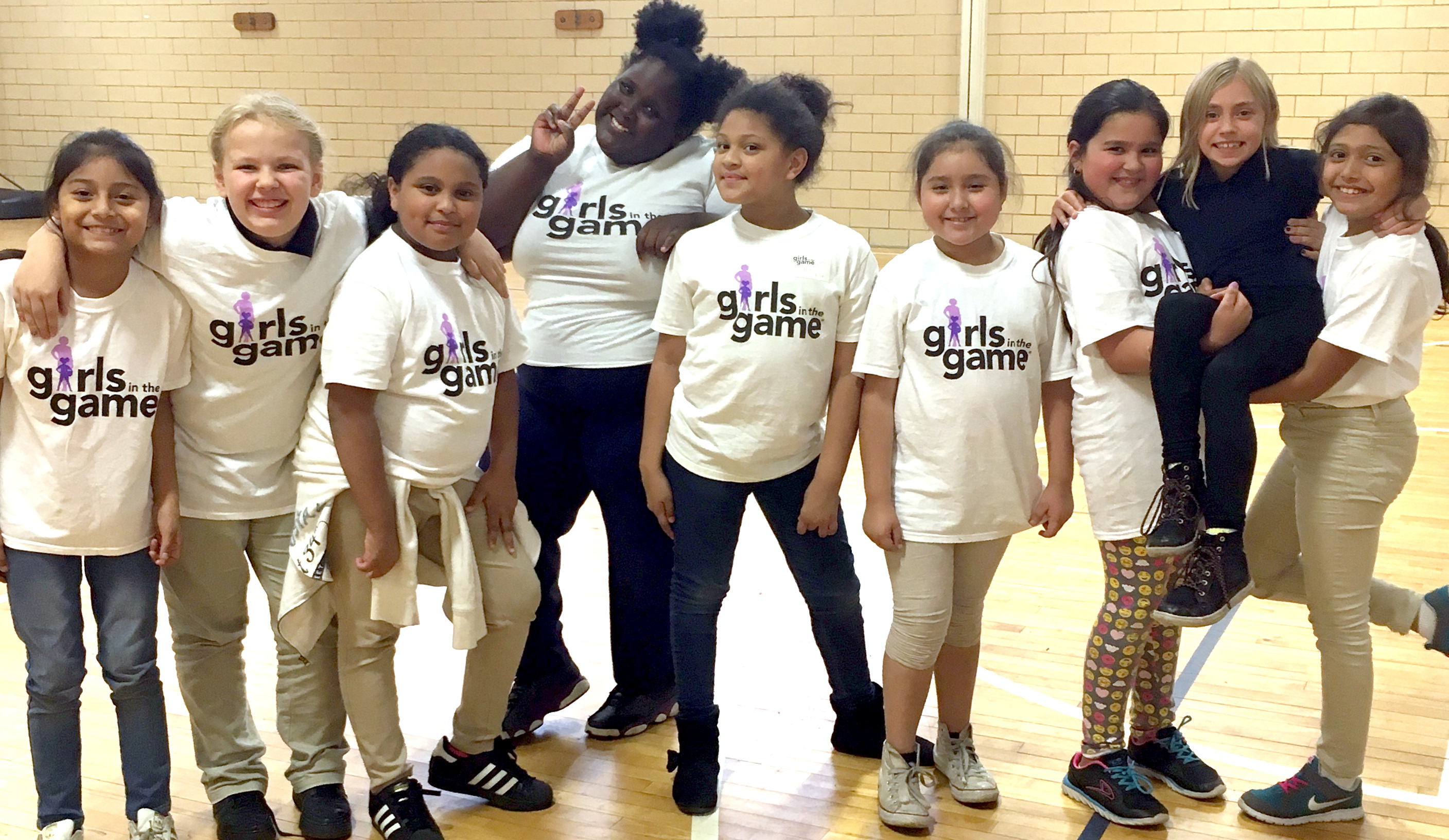 A group of girls wearing Girls in the Game T-shirts in a Gymnasium