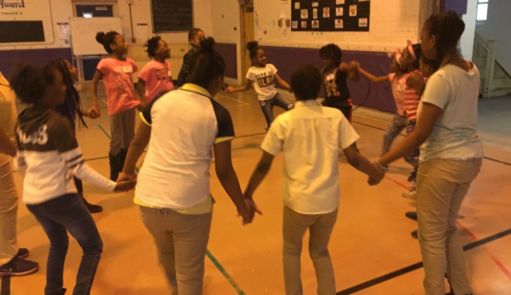 A group of girls holding hands in a circle in a gymnasium