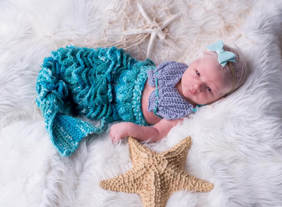 An infant in a mermaid tail outfit