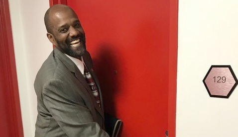 A smiling african american man in a suit opening a red door