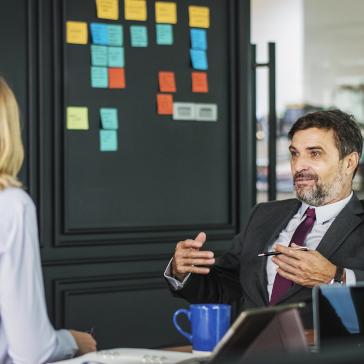 A man providing constructive feedback in front of an agile board