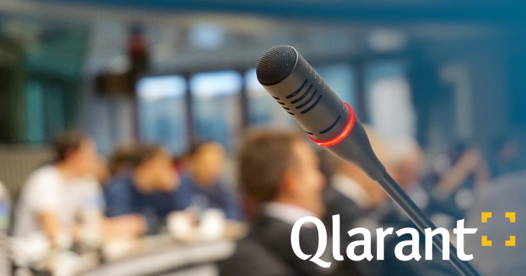 Qlarant logo overlaid on a microphone in a conference room