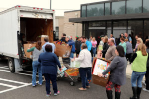 Qlarant Associates load gifts into a box truck