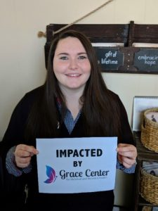 Young mother with brown hair smiling and holding a sign that reads Impacted by Grace Center