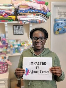Young, bespectacled, African American woman holding a sign that reads Impacted by Grace Center