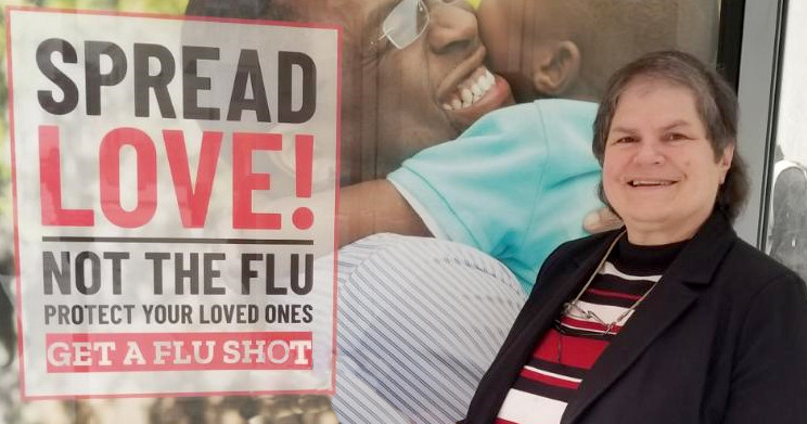 Jennifer Thomas smiling in front of a poster for flu vaccines