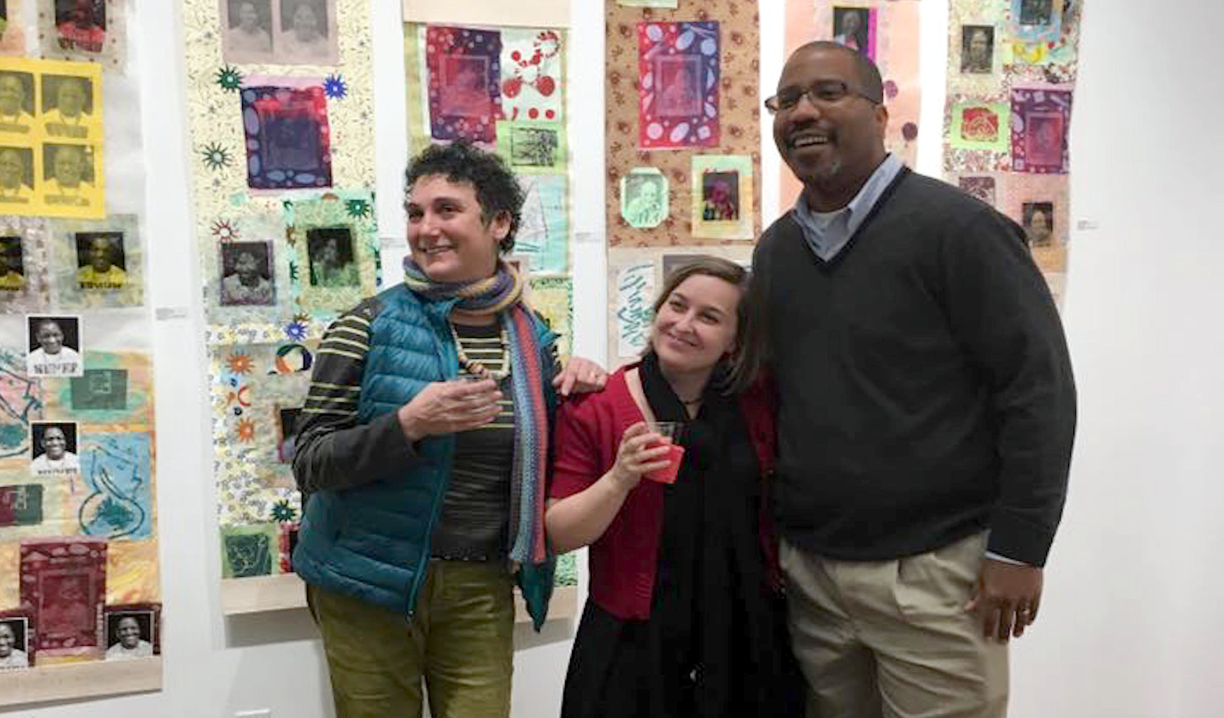 three people smiling holding drinks at an art gallery event