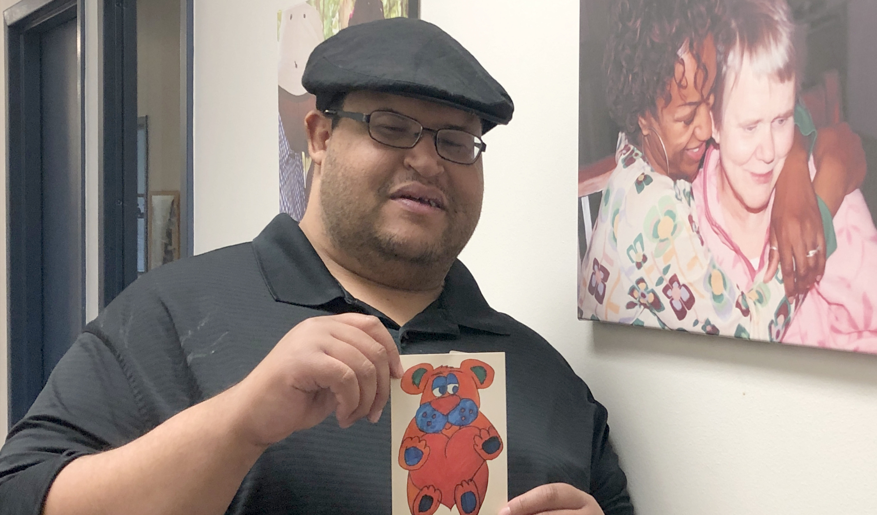 a client holding his artwork at the gallery. it's a small orange and blue bear