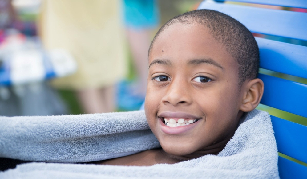 a young african-american boy wrapped in a towel smiling
