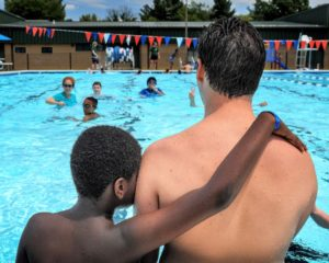 a young african american boy with his arm across the back of a caucasian man - both face away from the camera looking out over a pool of children