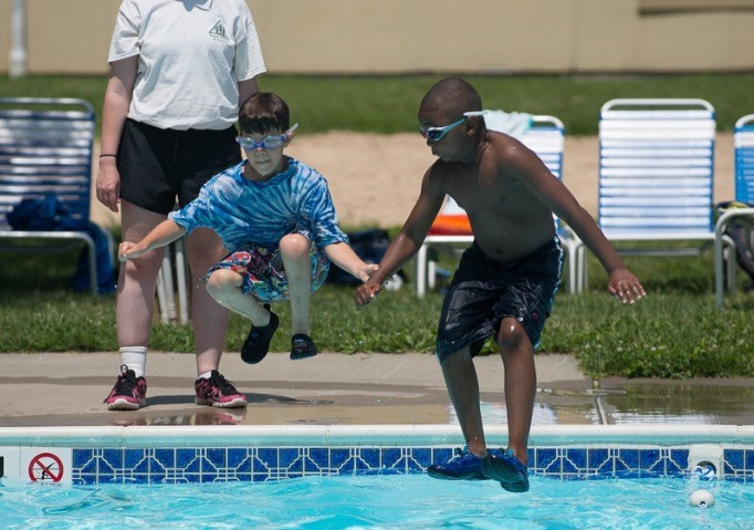 Two boys jump into a pool holding hands