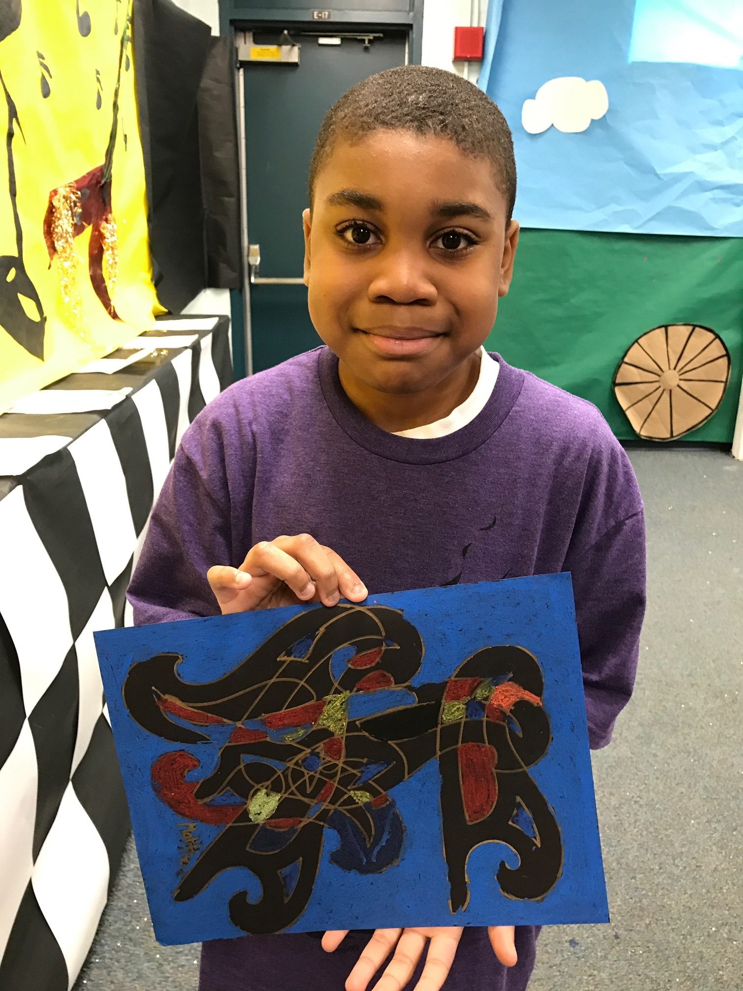 a young black boy holds his art