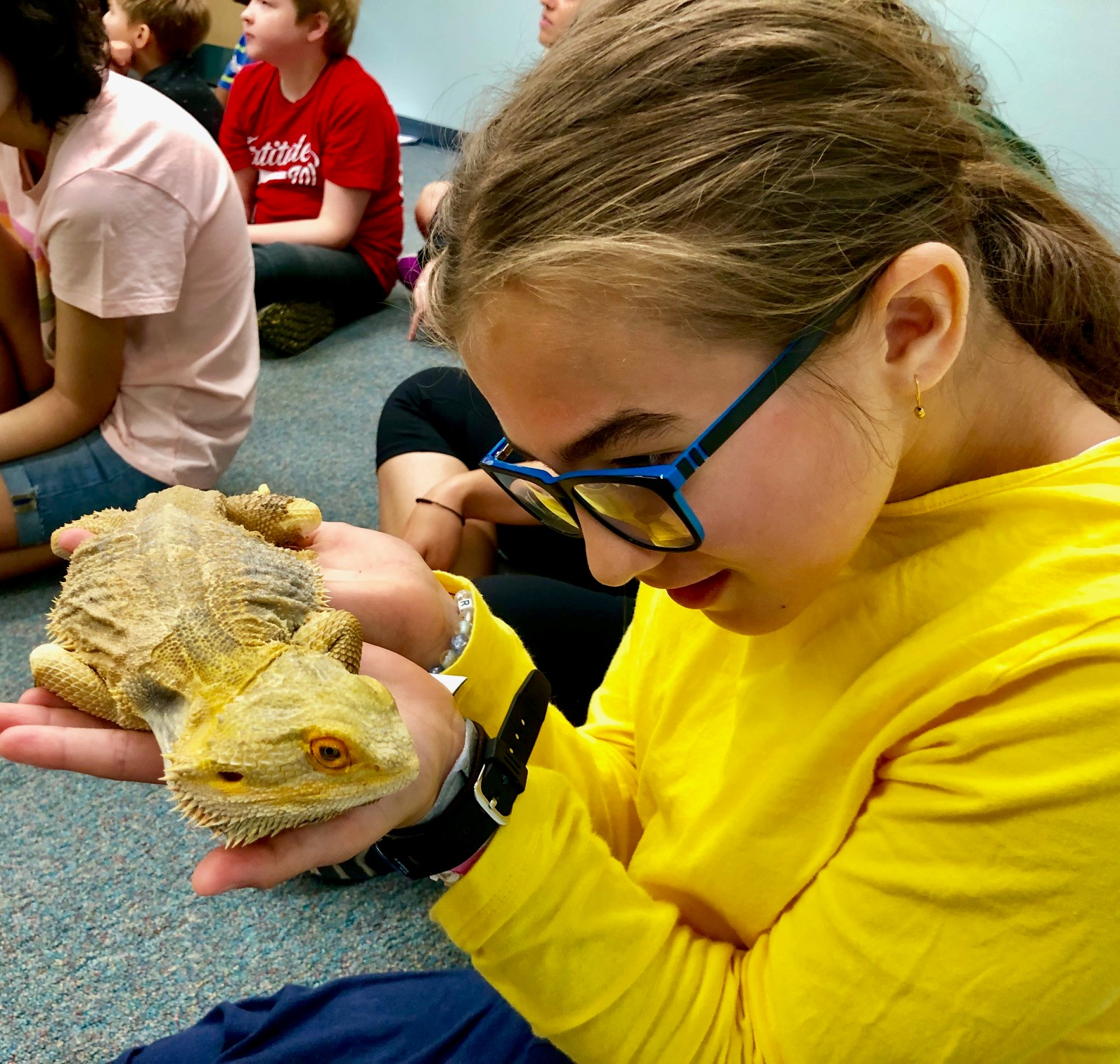 A girl with glasses holds a bearded dragon