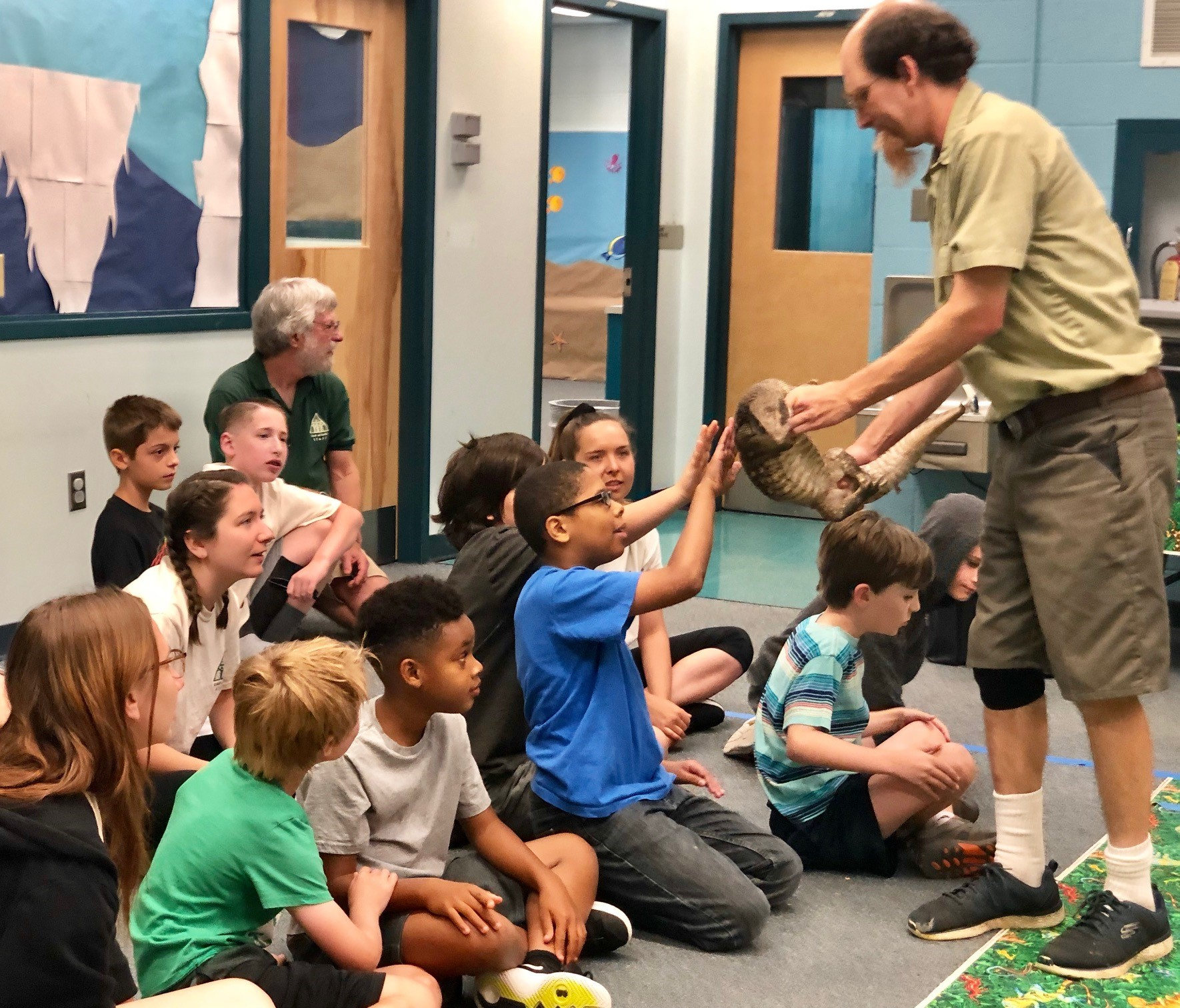 a group of kids touches a reptile held by a presenter