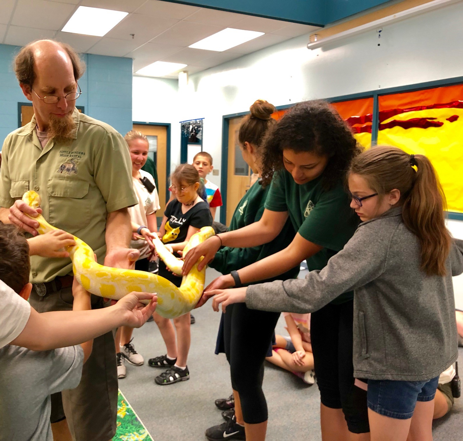 a group of girls touches a large snake held by a presenter