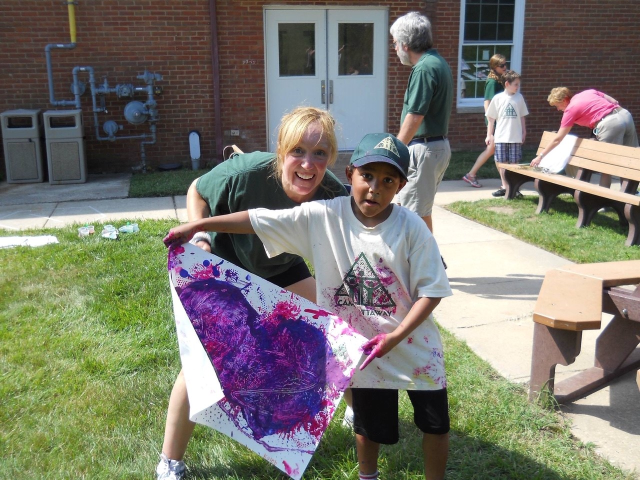 a young boy holds a painted purple heart poster posing with a camp counselor