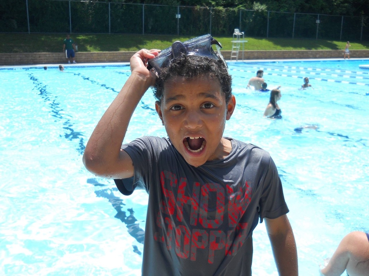 a young boy pulls the goggles off his head in front of a pool