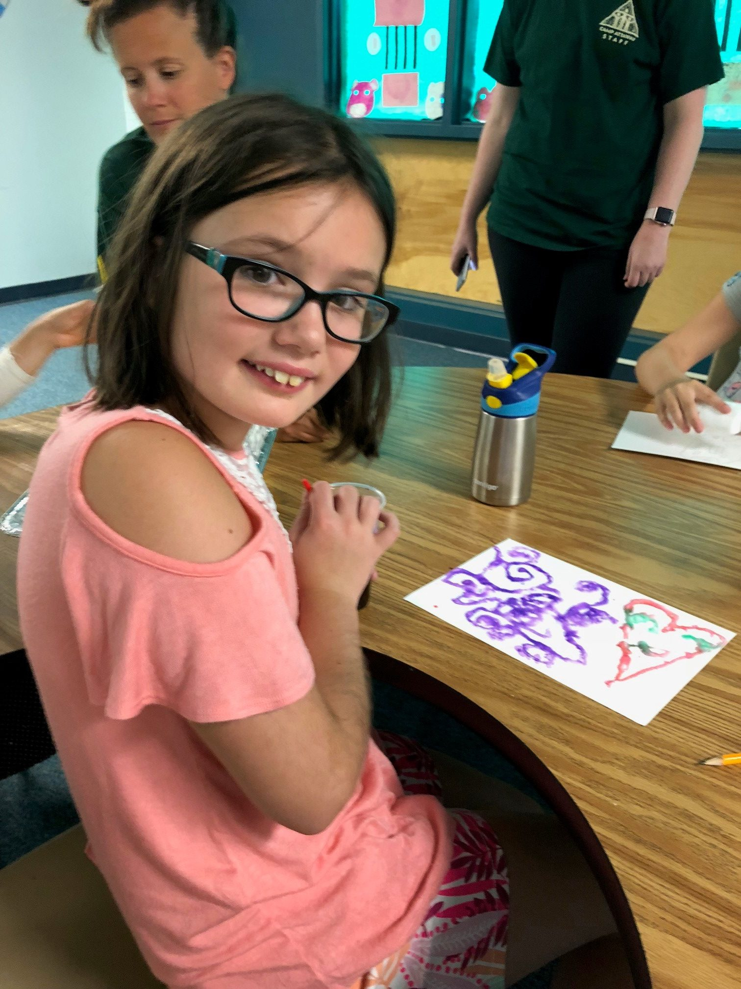 a girl in glasses shows off her art
