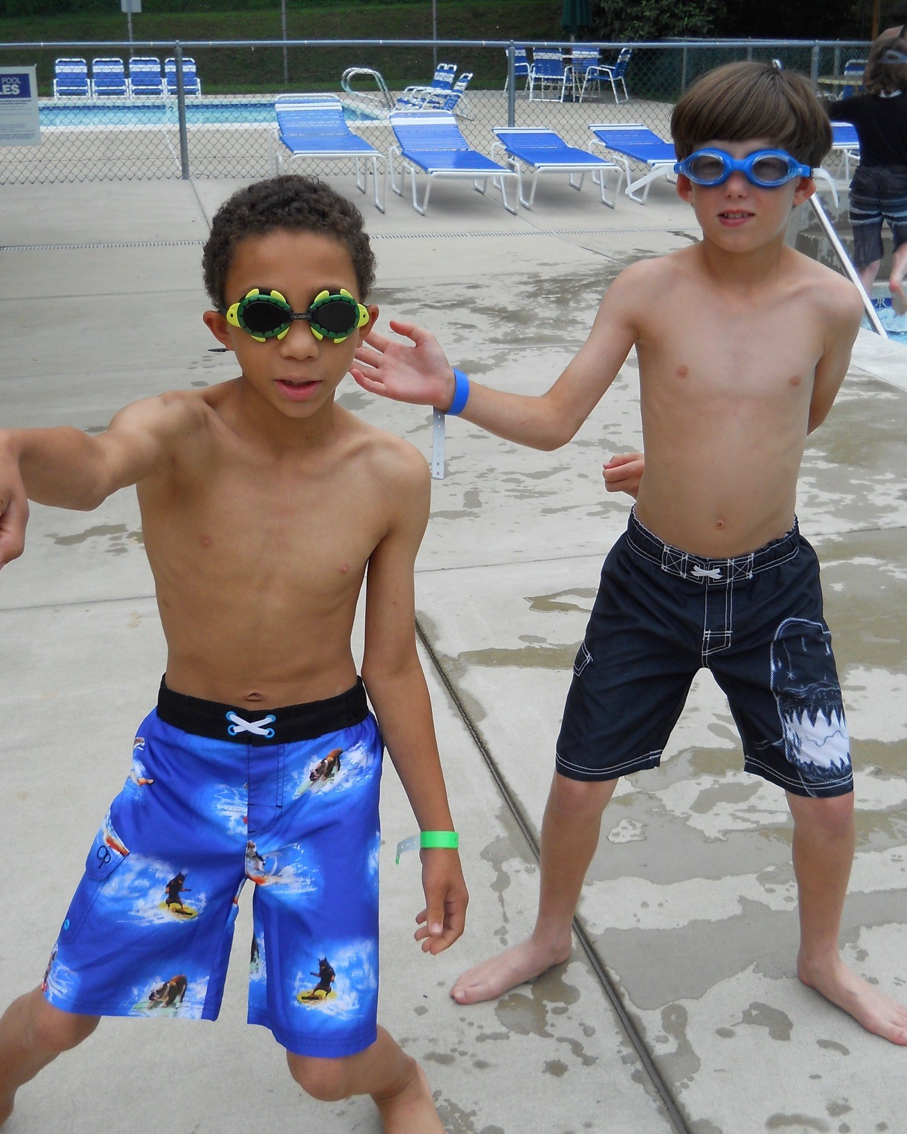 two boys dance wearing sunglasses at the pool