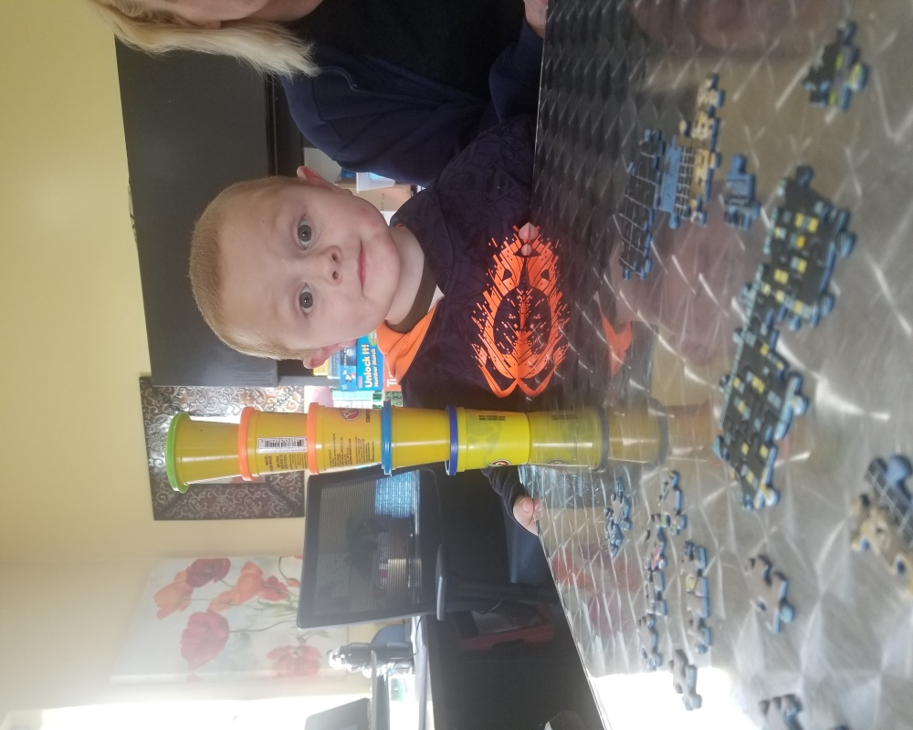 a toddler stacks play-doh containers
