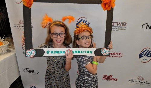 Two young girls holding a Kinera Foundation frame around their heads
