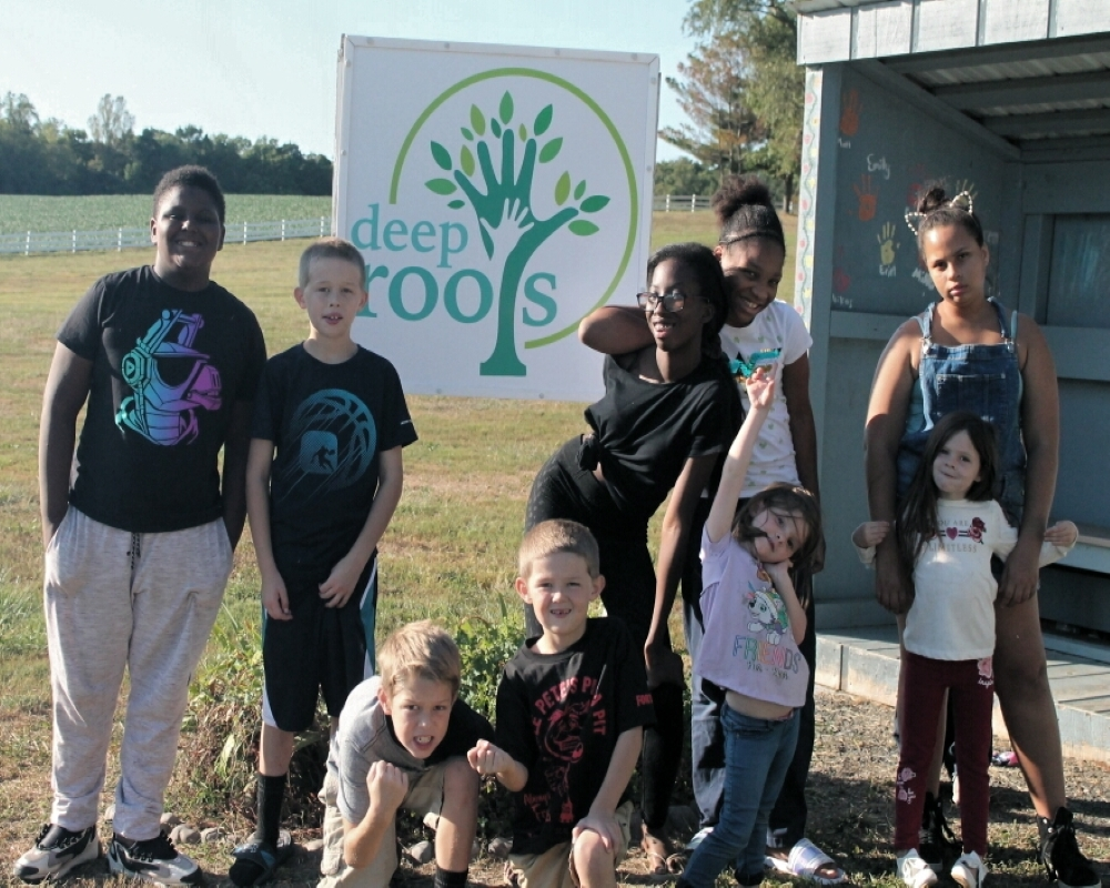 a group of women and kids in front of the Deep Roots sign