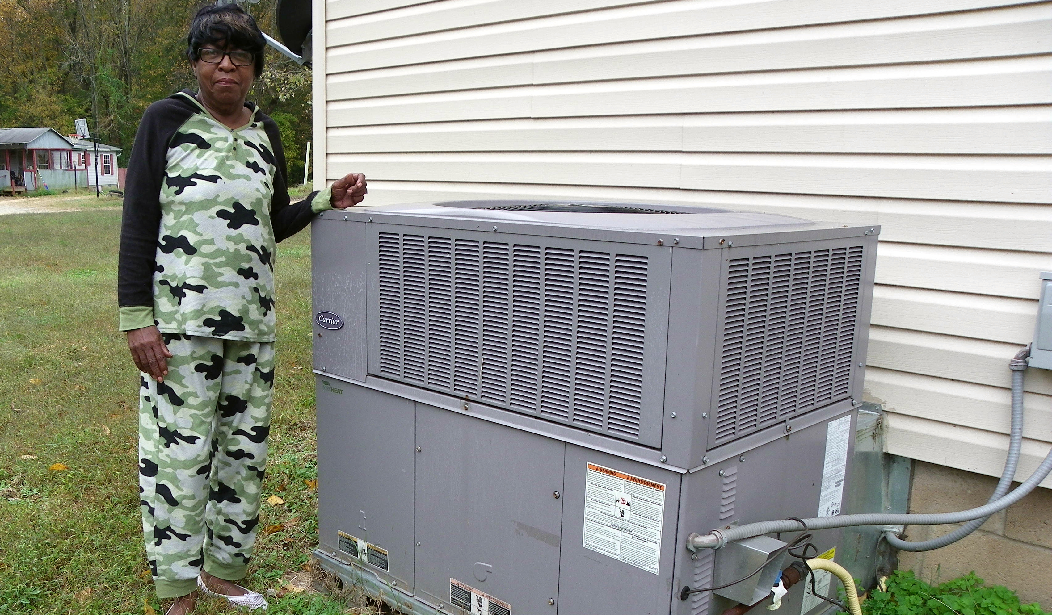 a woman stands with her hand on a new HVAC unit outside her home