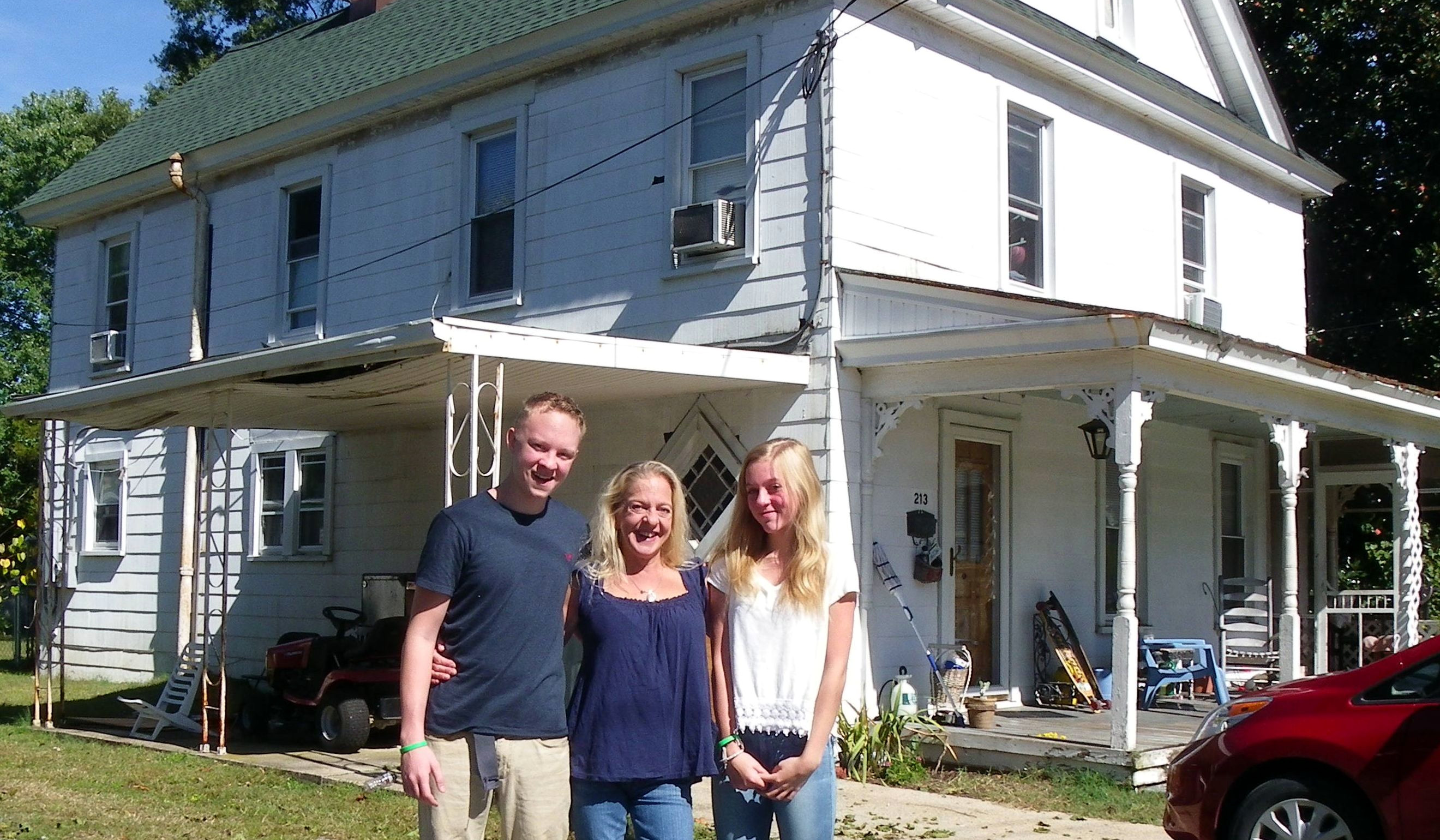 a mother and her son and daughter stand closely together in front of their renovated home