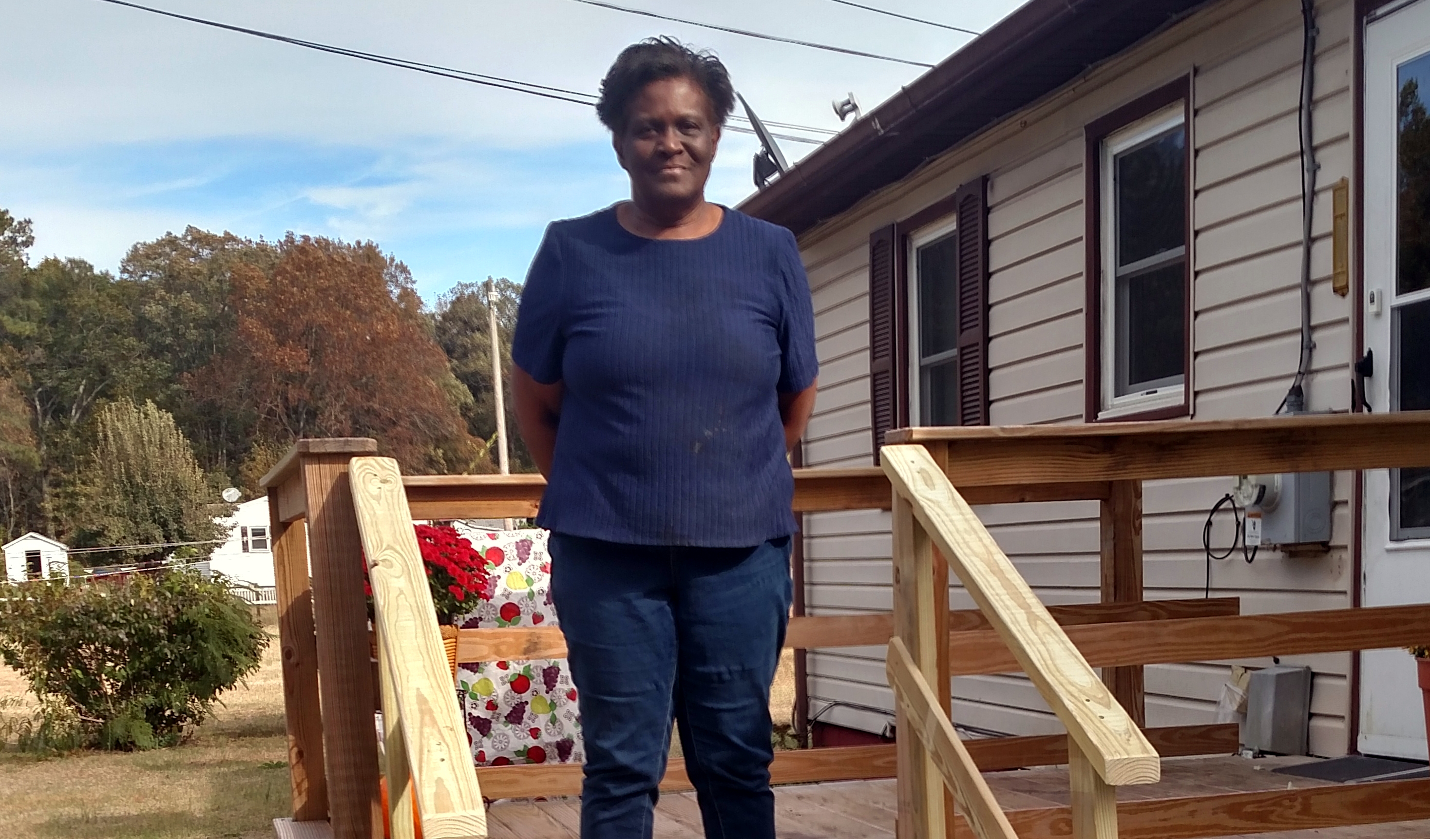 a woman stands on her new wooden porch