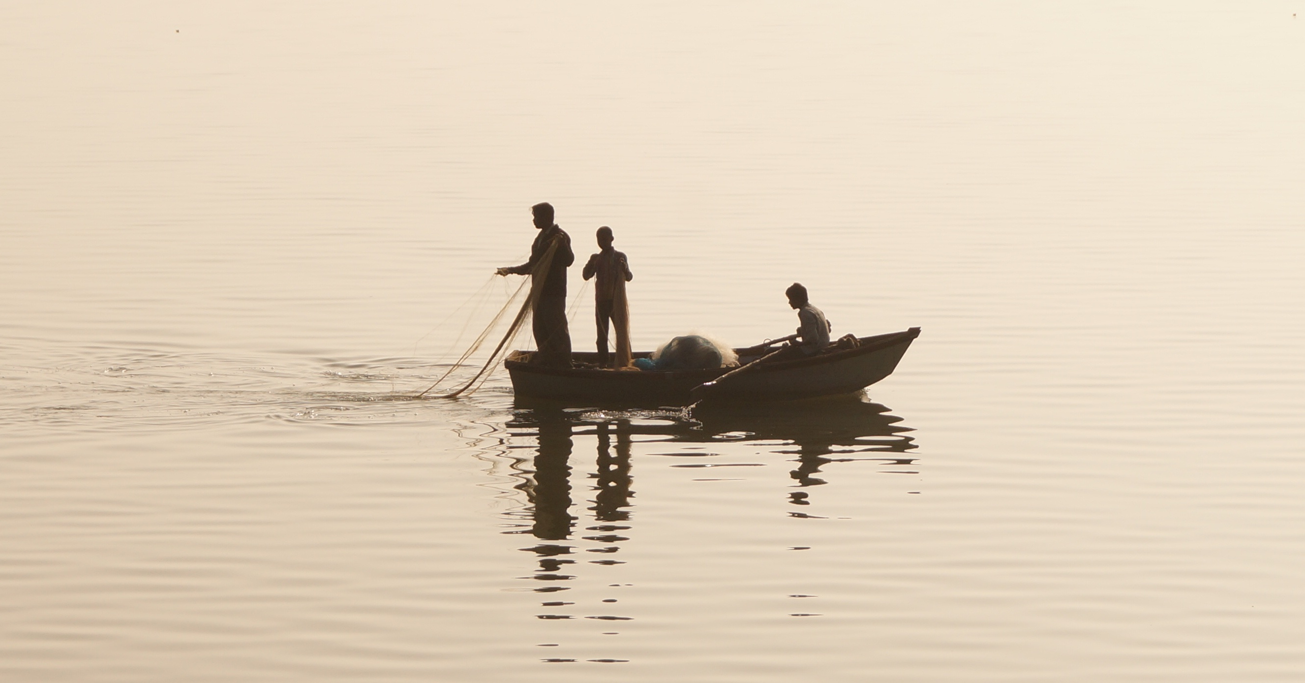 three people in a boat fishing