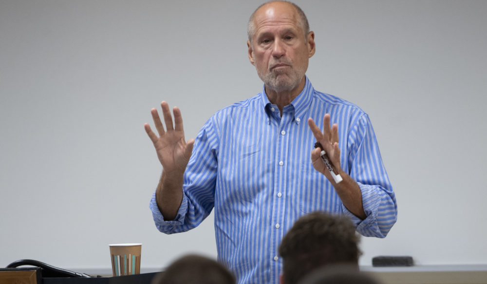 a man speaking to a group and gesturing