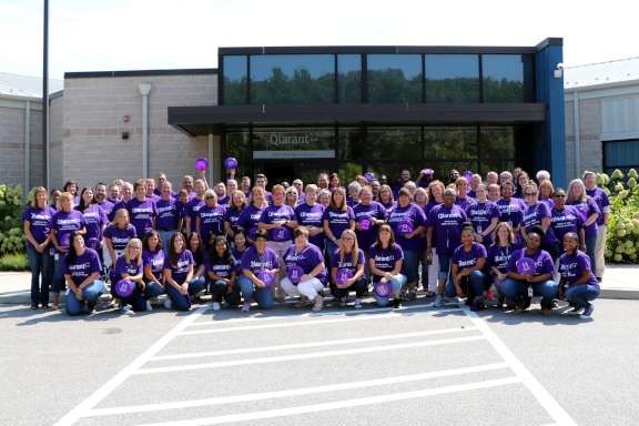 Large group of Qlarant associates all wearing purple shirts